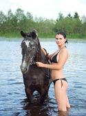 Girl bathe horse in a river — Stock Photo
