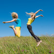 Woman jumping on meadow and blue sky — Stock Photo