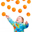 Baby girl caughts orange — Stock Photo