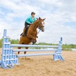 Girl riding horse and jumping — Stock Photo