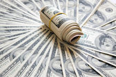 Rolled money cutout on a background dollars — Stock Photo