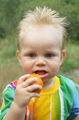The lovely boy with tangerine — Stock Photo