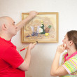 Couple hanging art picture on wall - Stock Photo