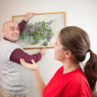 Couple hanging up an art picture - Stock Photo