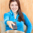 Stock Photo: Woman smiling with TV remote control