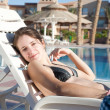 Girl near resort swimming pool — Stock Photo