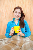 Girl relaxing with a yellow cup at home — Stock Photo