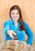 Woman smiling with TV remote control — Stock Photo