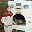 Stock Photo: Woman puts a pot into russian stove