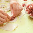 Rolling of meat stuffing into dough — Stock Photo