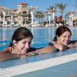 Girls in swimming pool at resort hotel — Stock Photo