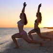 Girls doing yoga against sunset — Stockfoto