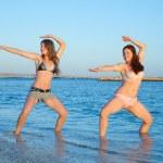 Girls practicing yoga during sunrise — Stock Photo