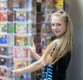 Girl in shop chooses disk — Stock Photo