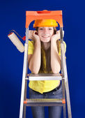 Girl with paint rollers on stepladder — Stock Photo