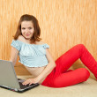 Girl with laptop on sofa — Stock Photo