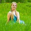Blonde girl relaxing in grass — Stock Photo