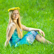 Stock Photo: Girl in chaplet is sitting in meadow