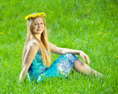 Girl in chaplet is sitting in meadow — Stock Photo