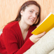 Pretty young girl reading book on sofa — Stock Photo