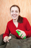 Woman cleaning a sheepskin with whisk broom — Stock Photo