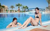 Girls in swimming pool at resort hotel — Stock Photo