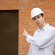 Builder pointing to door — Stock Photo