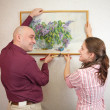 Couple hanging up an art picture on their wall — Stock Photo #3575507