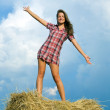 Stock Photo: Girl standing on straw bail