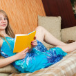 Girl reading book on sofa — Stock Photo