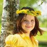 Girl in dandelion wreath near birch — Stock Photo #3576692