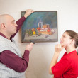 Young couple hanging art picture on wall at — Stock Photo