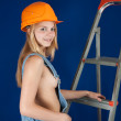 Sexy girl in dungarees and hardhat — Stock Photo