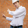 Foto Stock: Builder pointing to brick wall
