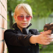 Woman aiming black gun — Stock Photo