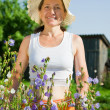 Woman gardener with bellflower — Stock Photo