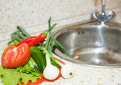 Vegetables on kitchen sink — Stock Photo