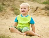 Boy sitting on sand — Stock Photo