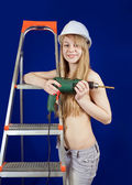 Topless girl in hard hat with drill — Stock Photo