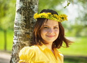 Girl in dandelion wreath near birch — Stock Photo
