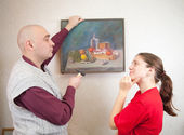 Young couple hanging art picture on wall at — Stockfoto