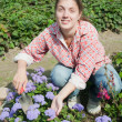 Smiling girl florists working in the garden — Stock Photo