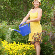 Stock Photo: Woman watering flowers
