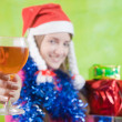 Stock Photo: Beautiful girl with champagne and present boxes over green