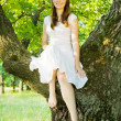 Girl sitting on tree — Stockfoto