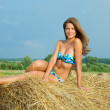 Girl laying  hay bail - Stock Photo