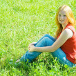 Teenager girl sitting in grass — Stock Photo