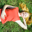 Teenager girl lying in grass - Stock Photo