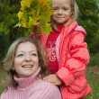 Happy woman with  daughter against fall — Stock Photo