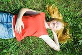 Teenager girl lying in grass — Stock Photo